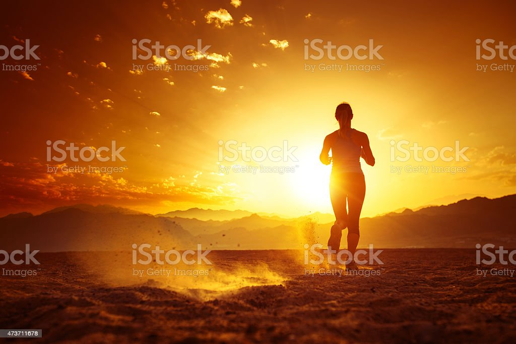 Silhouette of female running in sunlight stock photo