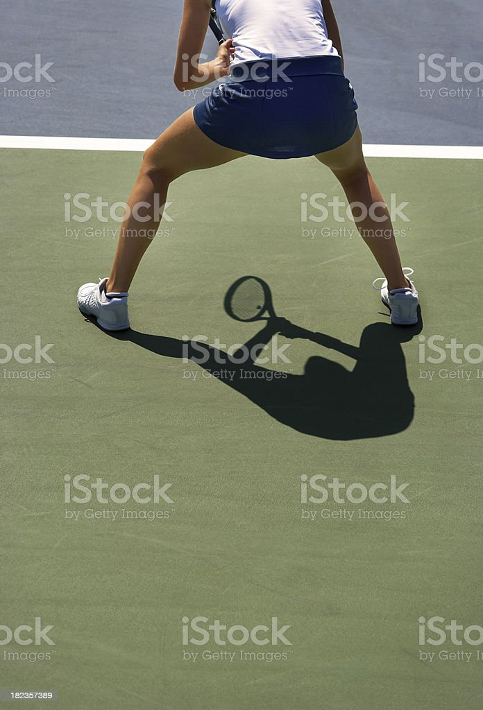 Silhouette of female tennis player returning serve position stock photo