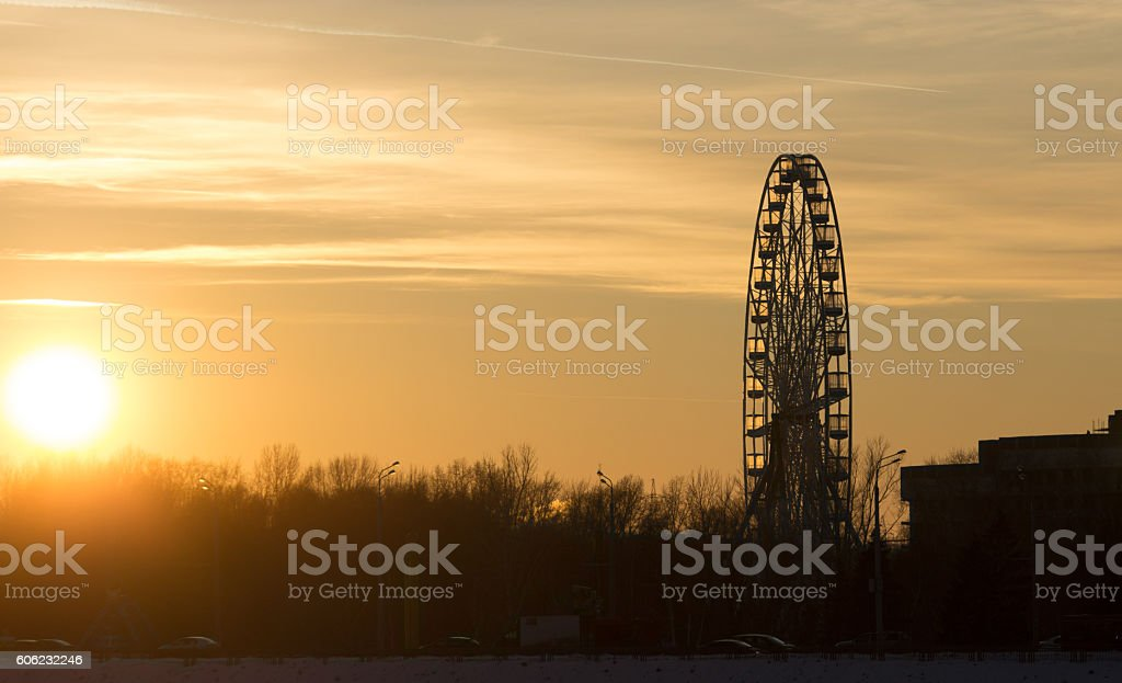 Silhouette of ferris wheel at sunset stock photo