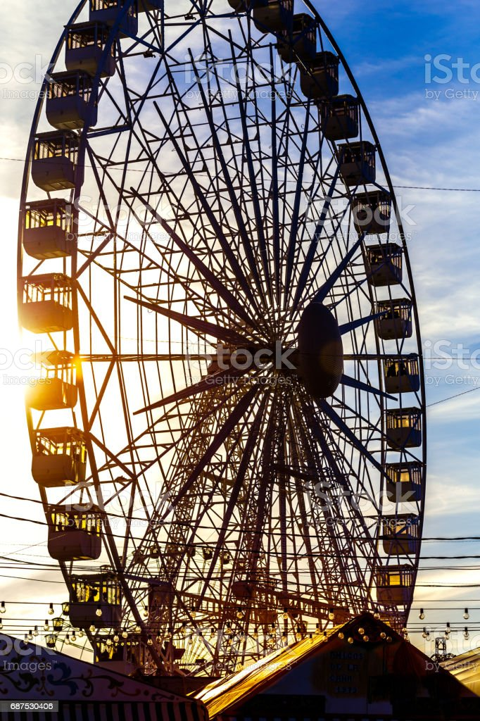 Silhouette of Ferris wheel at sunset. stock photo