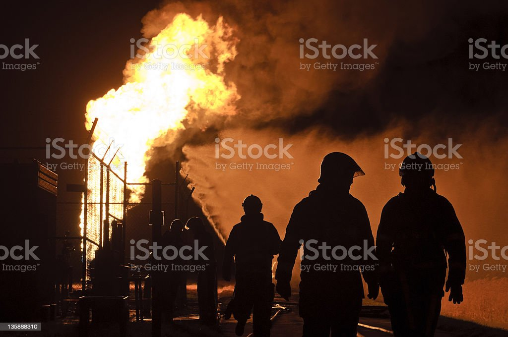 silhouette of firefighters in action by night royalty-free stock photo
