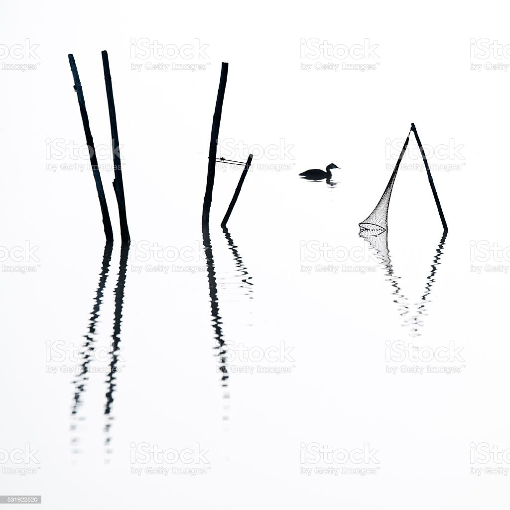 Silhouette of Fish trap reflecting on lake in fog stock photo