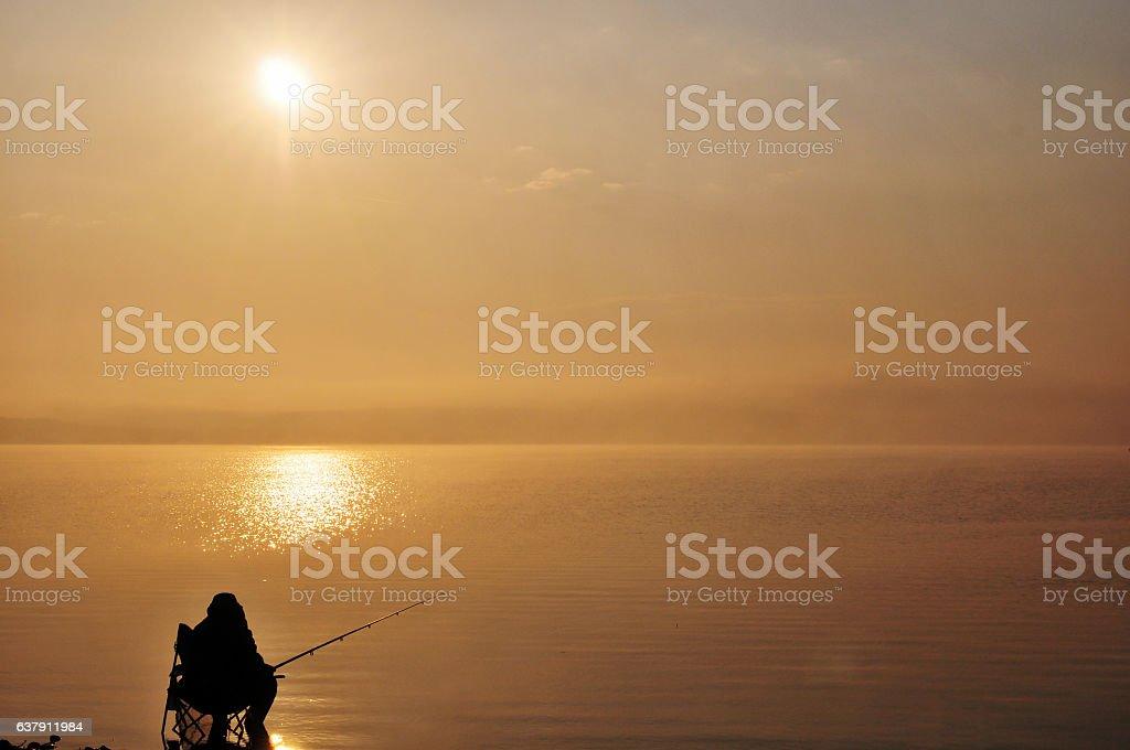 Silhouette of Fisherman at sunrise lake stock photo