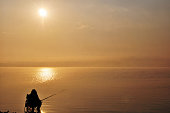 Silhouette of Fisherman at sunrise lake