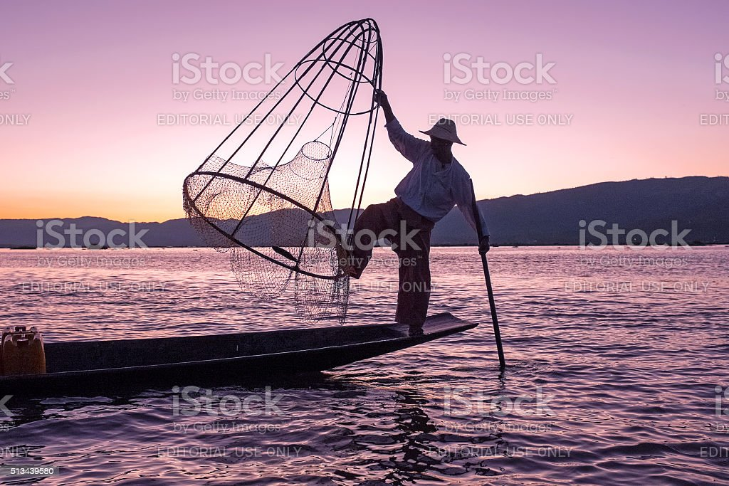 Silhouette of fisherman at sunset Inle Lake Burma Myanmar stock photo