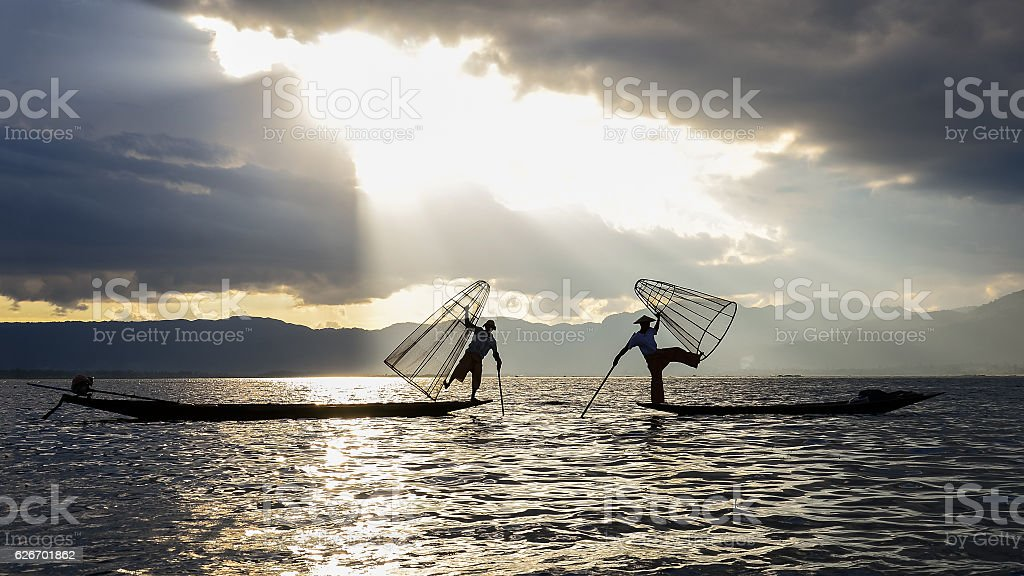 Silhouette of fisherman at sunset Inle Lake Burma Myanmar stock photo