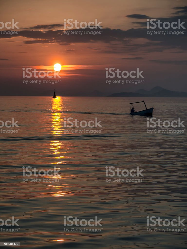 Silhouette of fisherman at the sunset stock photo