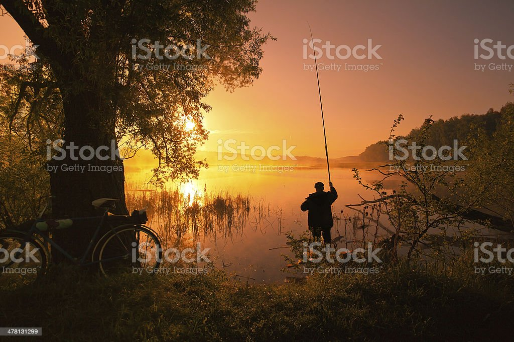 Silhouette of fisherman on the lake at sunset stock photo