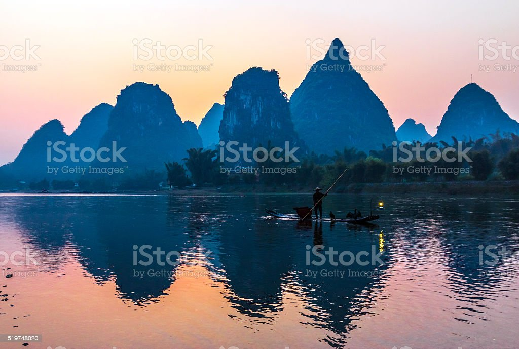 Silhouette of Fisherman with Cormorant Bird on Boat China River stock photo