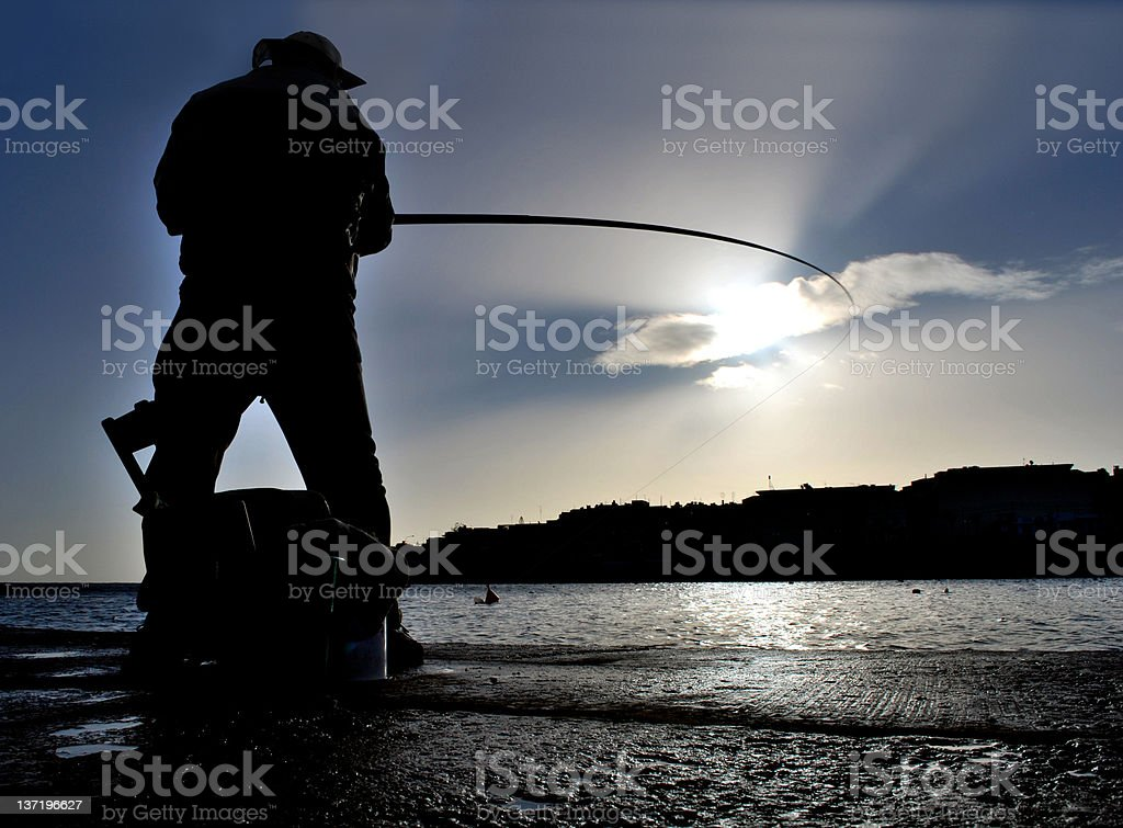 Silhouette of fisherman working stock photo