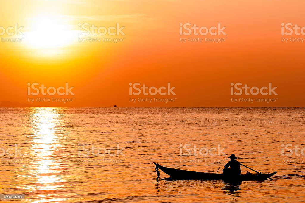 Silhouette of fishermen and his boat stock photo