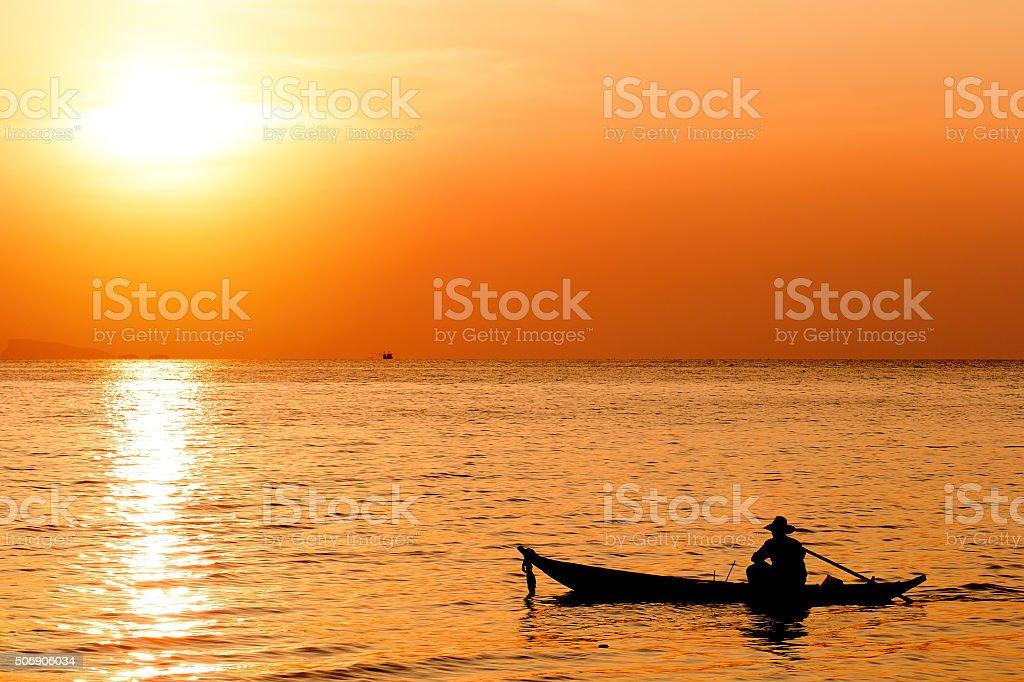 Silhouette of fishermen boat in sunset stock photo