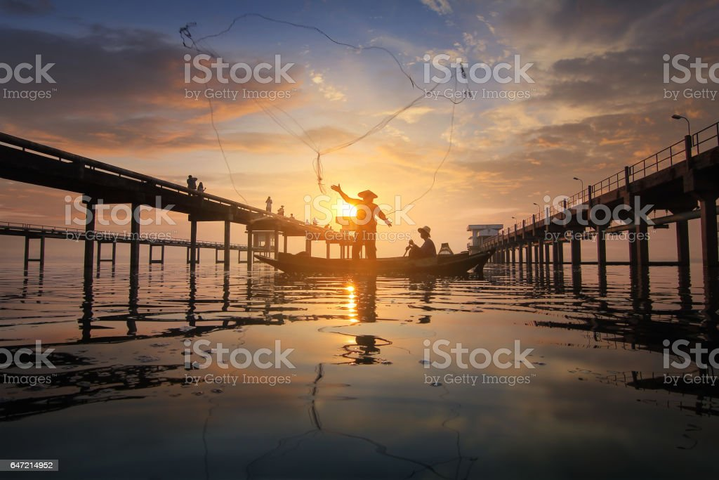 Silhouette of fishermen using nets to catch fish stock photo