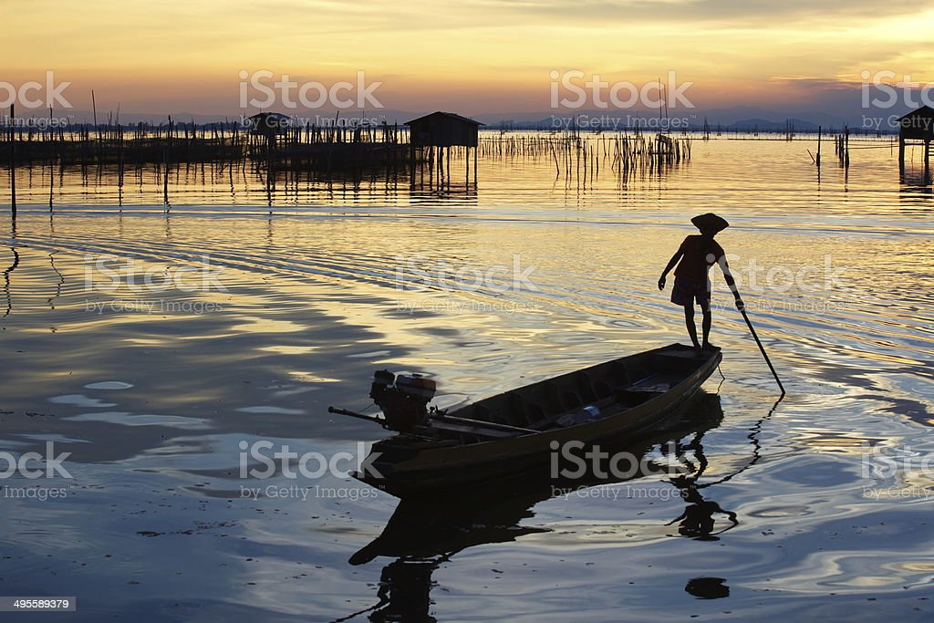 silhouette of fishermen with yellow and orange sun stock photo