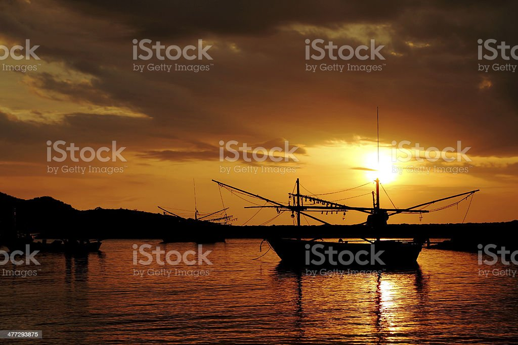 Silhouette of fishing boat at sunset stock photo