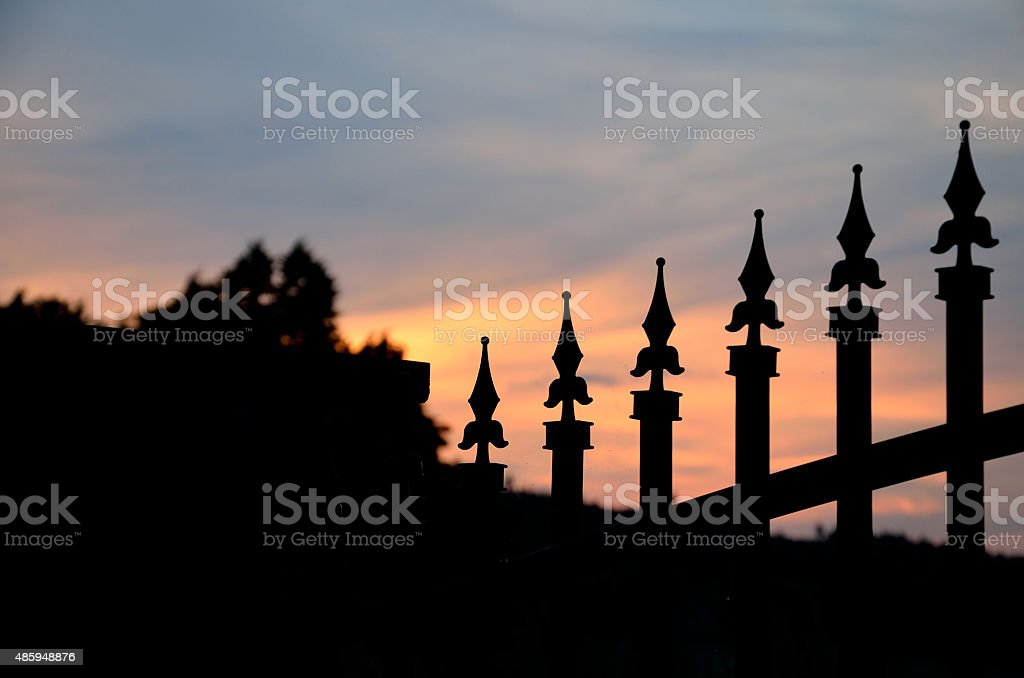 Silhouette of forged gate on orange evening sky stock photo