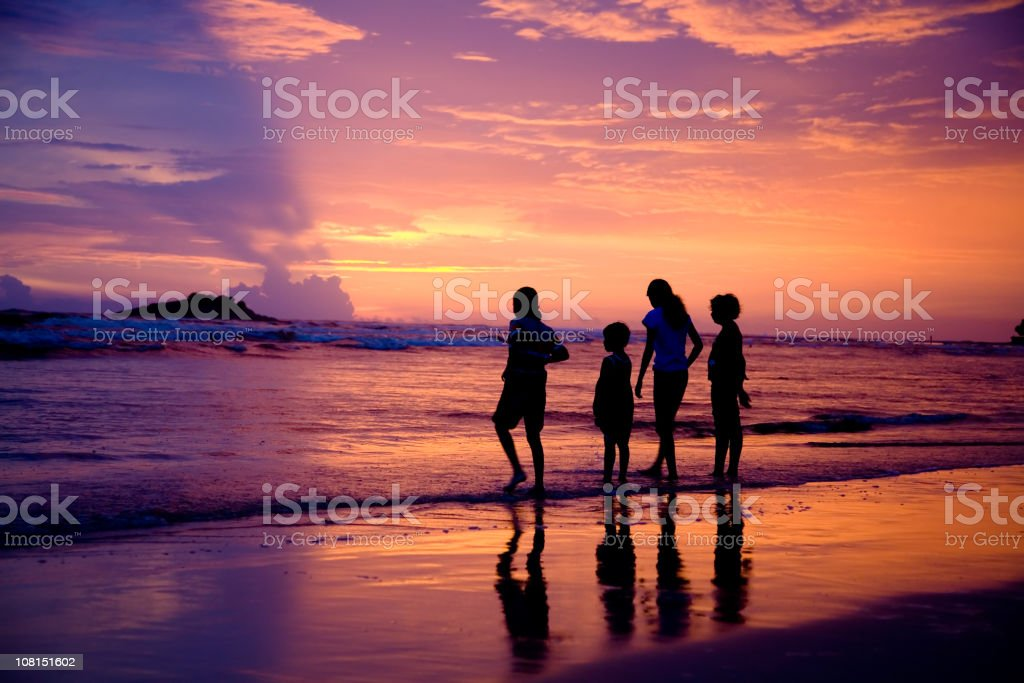 Silhouette of Four Children on Beach at Sunset royalty-free stock photo
