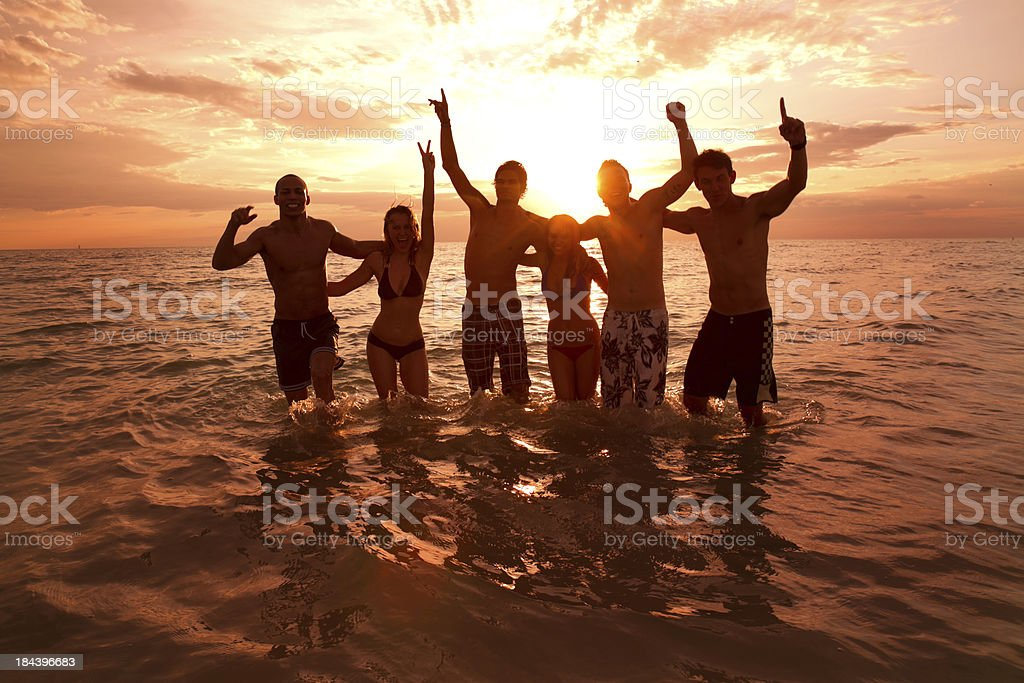 A silhouette of friends in the sea at sunset stock photo