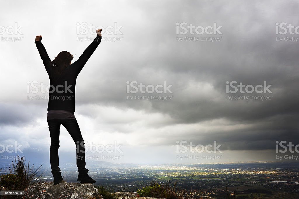 Silhouette of girl on hill's crest, arms raised in triumph stock photo