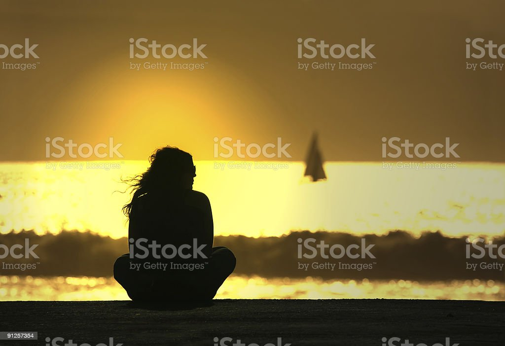 Silhouette of girl sitting in front of harbour at sunset royalty-free stock photo