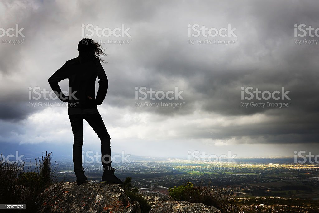 Silhouette of girl under stormy sky looking towards sunlit area stock photo