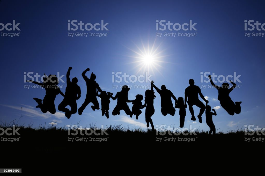 Silhouette of group of people jumping against the blue sky. stock photo