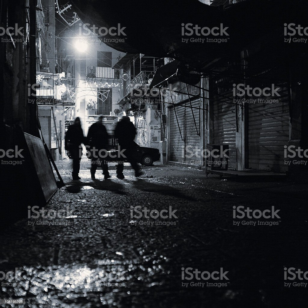 Silhouette of Group Walking Through Alley at Night royalty-free stock photo