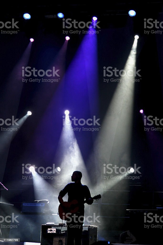 Silhouette of guitar player against strobe lights at concert stock photo