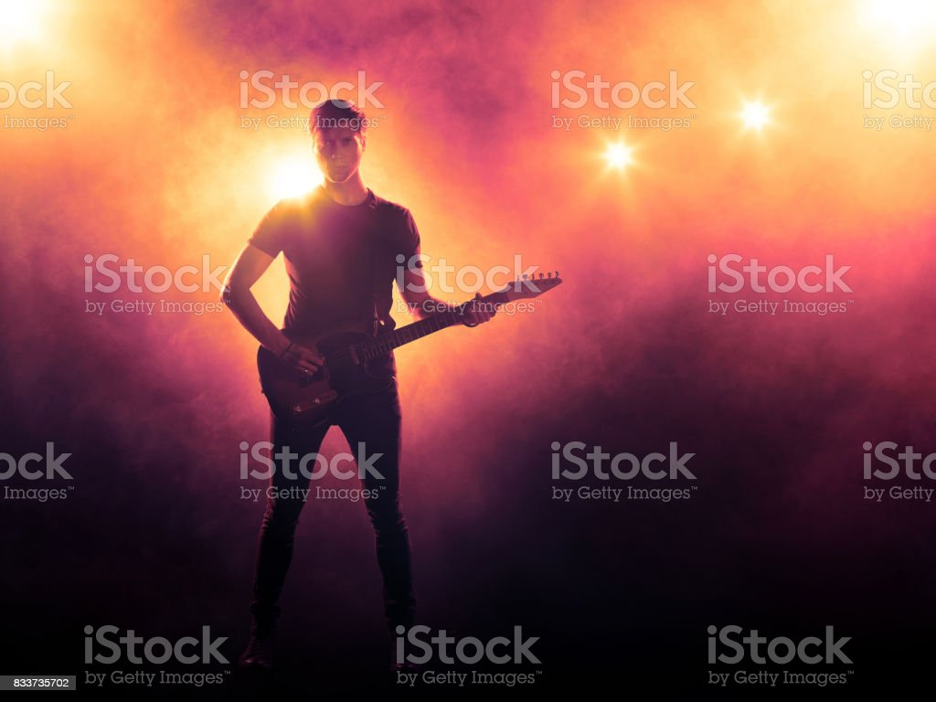 Silhouette of guitar player on stage stock photo