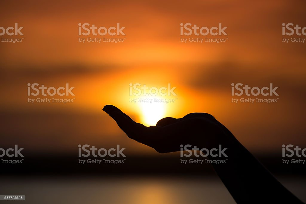 Silhouette of hand holding sun stock photo