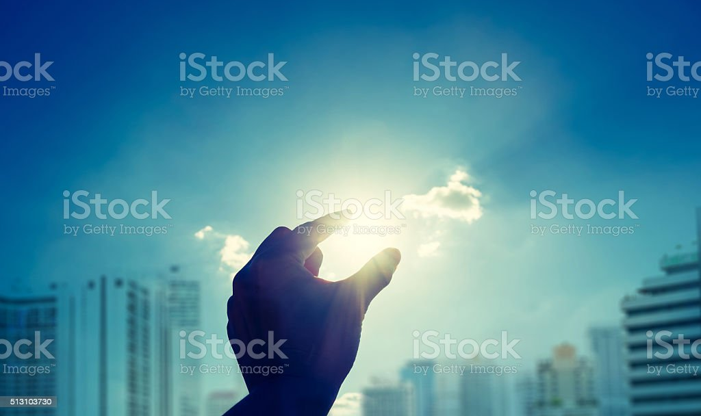 Silhouette of Hand picking sun with blue sky and cloud stock photo