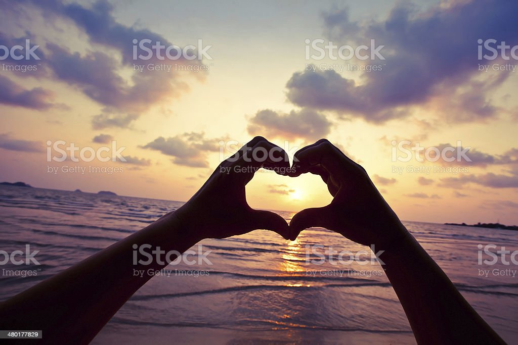 Silhouette of hands forming a heart around the sun stock photo