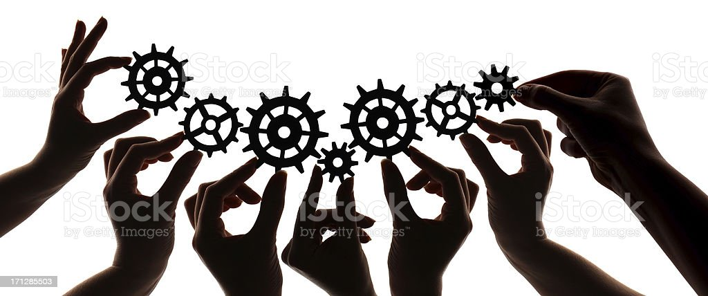 Silhouette of hands holding cogs and gears stock photo