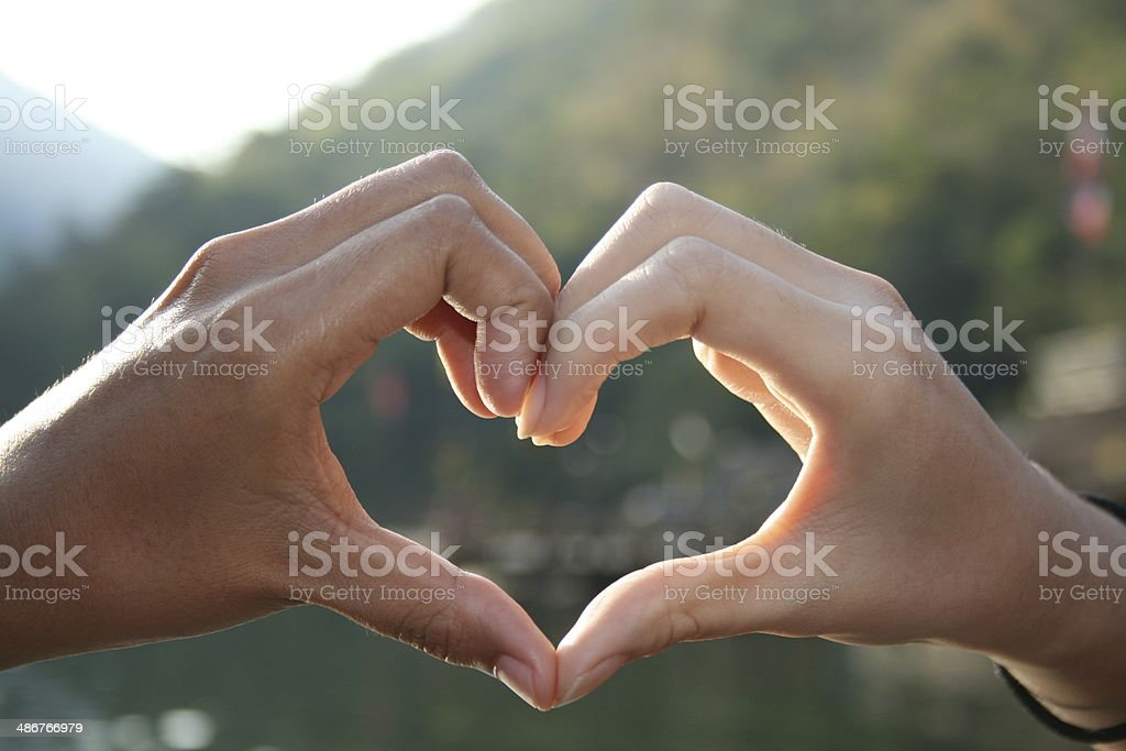 Silhouette of hands in heart shape stock photo