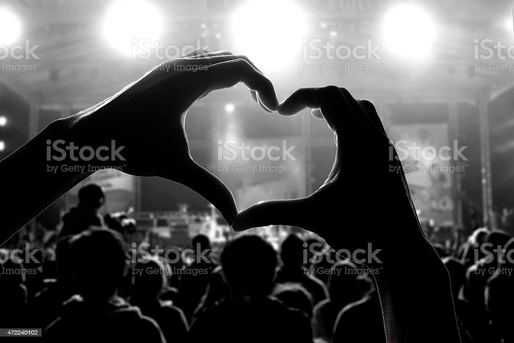 Silhouette of hands making a heart at a concert stock photo