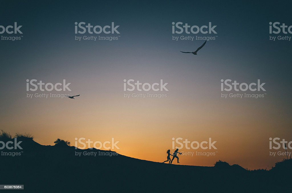 Silhouette of happy couple running at sunset стоковое фото