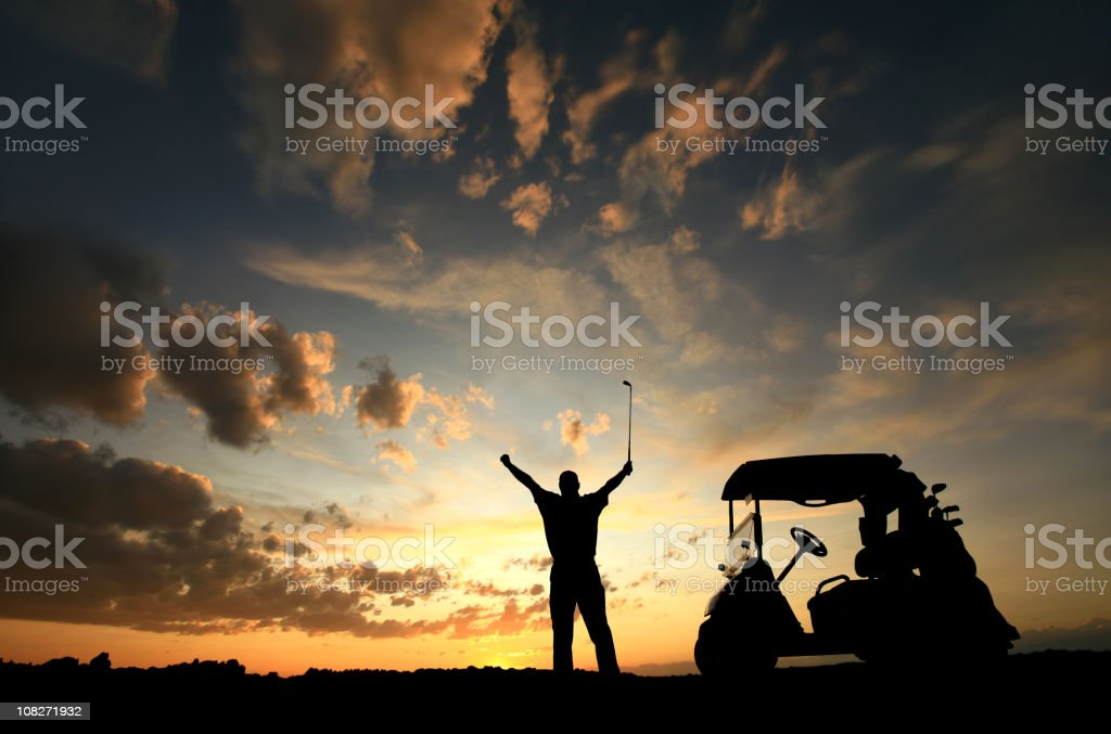 Silhouette of happy golfer with arms raised and golf cart royalty-free stock photo