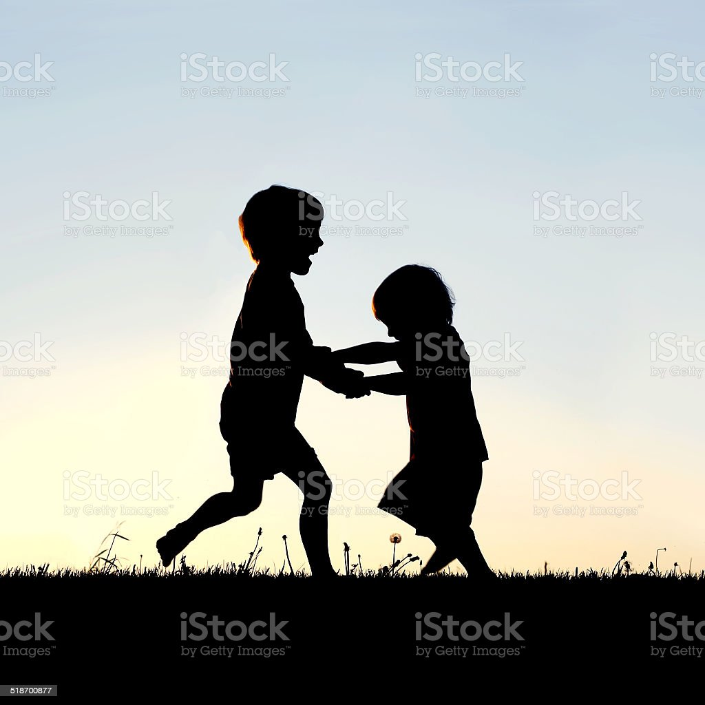 Silhouette of Happy Little Children Dancing at Sunset stock photo