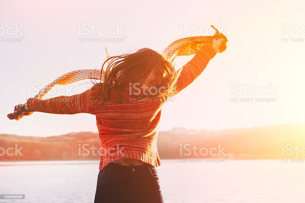 Silhouette of happy teen girl jumping stock photo