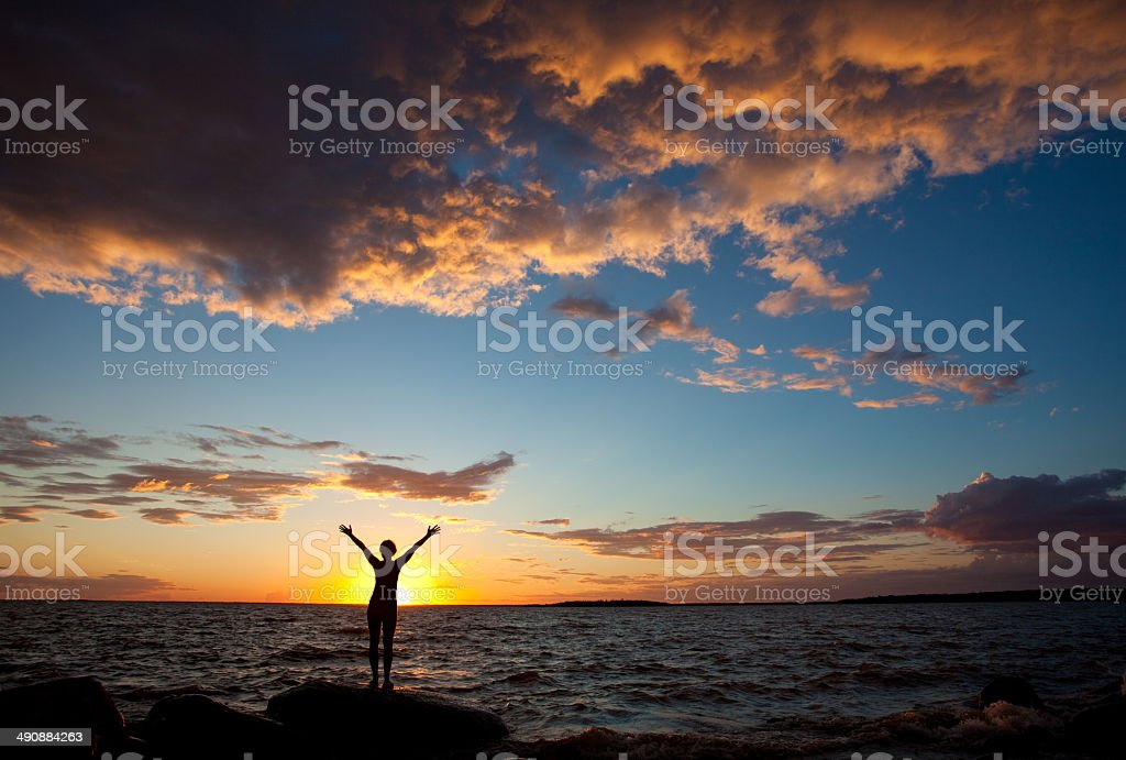 Silhouette of Happy Woman Standing by the Sea stock photo