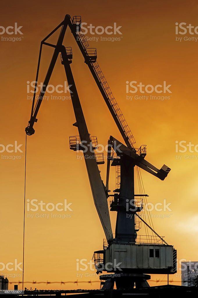 Silhouette of harbor crane at sunrise. stock photo