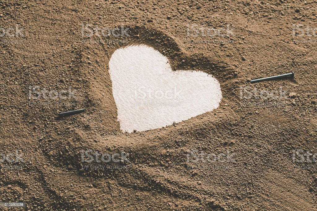Silhouette of heart drawn in the sand clay stock photo