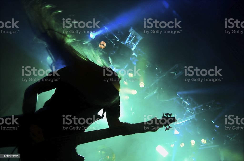 Silhouette of heavy metal guitar player performing live stock photo