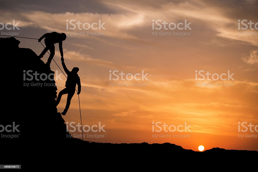 Silhouette of helping hand between two climber stock photo