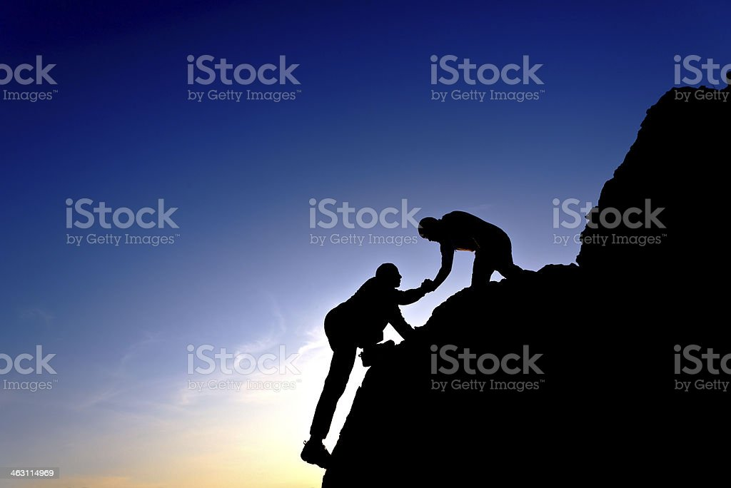 Silhouette of helping hand between two climbers stock photo