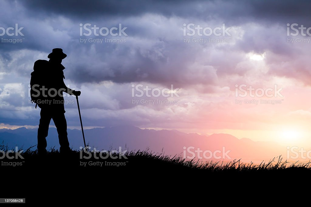 Silhouette of hiker in mountains with sunset royalty-free stock photo