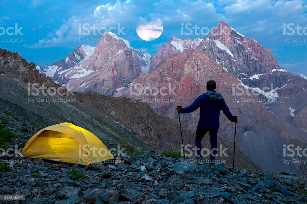Silhouette of Hiker with illuminated tent and twilight Sky stock photo