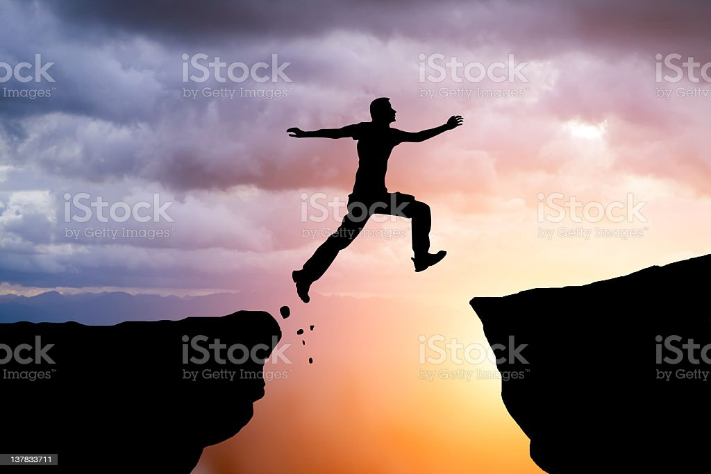 Silhouette of hiking man jumping over the mountains stock photo