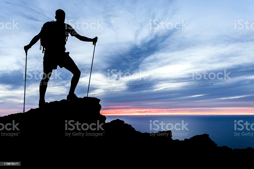 Silhouette of hiking man on top of rock near sea at sunset royalty-free stock photo