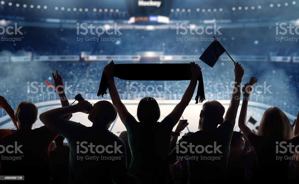 Silhouette of hockey fans at a stadium stock photo